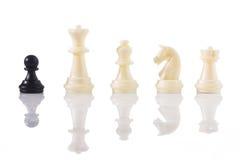 Uno contra todos - un empeño negro con los pedazos de ajedrez blancos Fotos de archivo