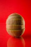 Uno cortó la fruta de kiwi en el fondo rojo, tiro vertical Imágenes de archivo libres de regalías