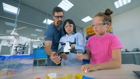 Uno de dos niños está llevando a cabo un quadcopter y un especialista la está dando instrucciones sobre él almacen de video