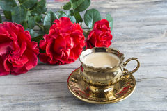 Uno doró la taza de café y de tres rosas rojas Imágenes de archivo libres de regalías