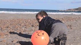 Uno e mezzo neonato di un anno che gioca sulla spiaggia con le pietre e la palla stock footage