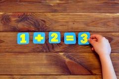 Uno más dos iguales tres Un ejemplo matemático El niño lleva a cabo una figura de papel Fondo de madera de Brown Fotos de archivo