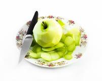 Uno peló la manzana verde con el cuchillo en una placa blanca y un fondo blanco Fotos de archivo libres de regalías
