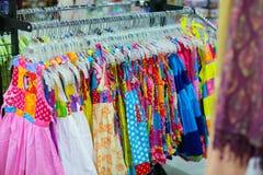 Uno scaffale delle camice variopinte ha appeso per la vendita ad una fiera Immagine Stock Libera da Diritti