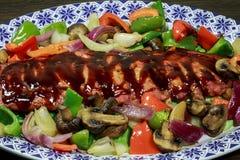 Uno scaffale delle costole ha cucinato con le verdure dell'arrosto e della salsa barbecue immagini stock libere da diritti