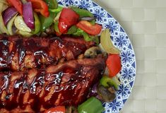 Uno scaffale delle costole ha cucinato con le verdure dell'arrosto e della salsa barbecue fotografia stock