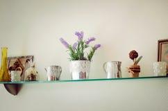 Uno scaffale di vetro con gli elementi decorativi sulla parete nella stanza Interiore moderno fotografie stock