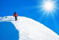 Uno scalatore che raggiunge la sommità fotografia stock