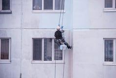 Uno scalatore del lavoratore dipinge un grattacielo residenziale e le guarnizioni sui giunti in una casa, dipingente una casa res fotografia stock libera da diritti