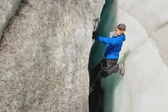 Uno scalatore libero senza assicurazione con due piccozze da ghiaccio aumenta da una crepa nel ghiacciaio Scalata libera senza co fotografia stock libera da diritti