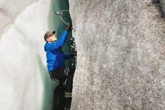 Uno scalatore libero senza assicurazione con due piccozze da ghiaccio aumenta da una crepa nel ghiacciaio Scalata libera senza co fotografia stock