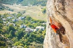 Uno scalatore in un cappello su una roccia Fotografia Stock