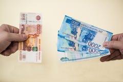 Uno scambio di cinque mila banconote russe per più piccoli soldi in due e mille rubli Fotografie Stock