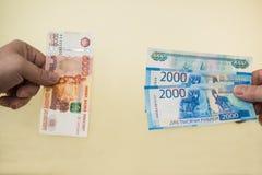Uno scambio equivalente di un cinque mila banconote russe per più piccoli soldi in due e mille rubli Nuovi soldi fotografia stock libera da diritti