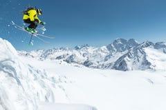 Uno sciatore in articolo sportivo pieno salta nel precipizio dalla cima del ghiacciaio contro lo sfondo del blu Fotografia Stock Libera da Diritti