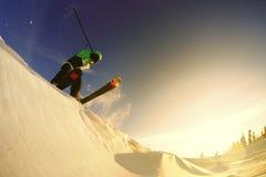 Uno sciatore del tipo fa un trucco contro il tramonto Immagine Stock