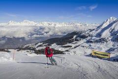 Uno sciatore in jeans che vanno in discesa una pista con la vista panoramica di largamente e la pista governata dello sci La vist Fotografia Stock Libera da Diritti