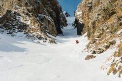 Uno sciatore maschio freerider con una barba discende il remoto all'alta velocità dal pendio Immagine Stock