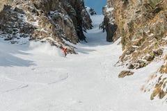 Uno sciatore maschio freerider con una barba discende il remoto all'alta velocità dal pendio Immagine Stock Libera da Diritti