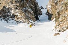 Uno sciatore maschio freerider con una barba discende il remoto all'alta velocità dal pendio Immagini Stock