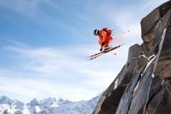 Uno sciatore professionista fa una salto-goccia da un'alta scogliera contro un cielo blu che lascia una traccia della polvere del Immagine Stock
