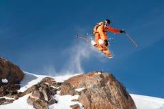 Uno sciatore professionista fa una salto-goccia da un'alta scogliera contro un cielo blu che lascia una traccia della polvere del Immagini Stock