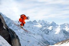 Uno sciatore professionista fa una salto-goccia da un'alta scogliera contro un cielo blu che lascia una traccia della polvere del Fotografia Stock