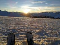 Uno sciatore stanco guarda il tramonto in Tavate, Svizzera fotografie stock