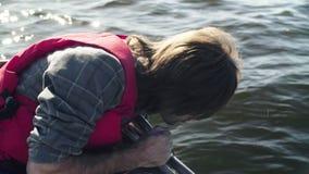 Uno scienziato che misura la profondità del lago facendo uso di un dispositivo speciale stock footage
