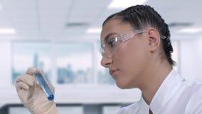 Uno scienziato femminile sta effettuando le prove di laboratorio di un liquido blu in una provetta mentre si sedeva ad una tavola archivi video