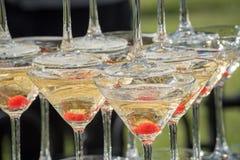 Uno scorrevole di champagne Piramide dei vetri del champagne con le ciliege rosse Immagini Stock