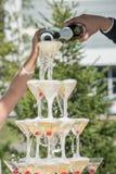 Uno scorrevole di champagne Piramide dei vetri del champagne con le ciliege rosse Fotografia Stock