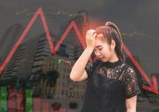 Uno sforzo e un'emicrania della donna dell'Asia quando caduta del mercato azionario Immagini Stock Libere da Diritti