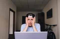 Uno sguardo alla macchina fotografica dal giovane stupito che si siede nella sua stanza vicino al monitor del computer Fotografie Stock Libere da Diritti