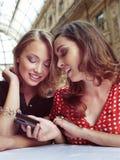 Uno sguardo di due amiche ai telefoni cellulari Fotografie Stock Libere da Diritti