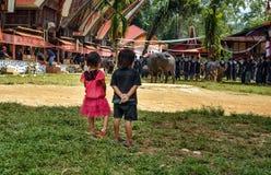 Uno sguardo di due bambini alla cerimonia funerea Tana Toraja Immagine Stock