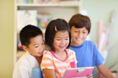 Uno sguardo di tre bambini ad un computer della compressa fotografie stock libere da diritti