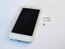Uno Smart Phone bianco, un vassoio di carta SIM e una piccola carta simulati As Fotografie Stock Libere da Diritti