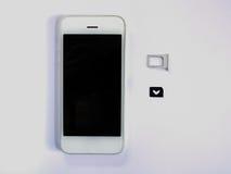 Uno Smart Phone bianco, un vassoio di carta SIM e una piccola carta simulati As Immagine Stock