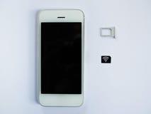 Uno Smart Phone bianco, un vassoio di carta SIM e una piccola carta simulati As Immagini Stock Libere da Diritti