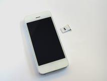 Uno Smart Phone bianco, un vassoio di carta SIM e una piccola carta simulati As Fotografia Stock Libera da Diritti