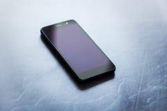 Uno Smart Phone con lo schermo sui precedenti di pietra grigi Immagini Stock Libere da Diritti