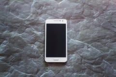 Uno Smart Phone con lo schermo sui precedenti di pietra grigi Fotografia Stock