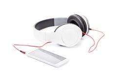 Uno Smart Phone si è collegato con le cuffie isolate su fondo bianco fotografia stock