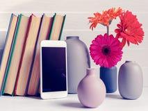 Uno smartphone bianco, parecchi libri, i vasi e un mazzo delle gerbere multicolori sono su un fondo di legno leggero Immagine Stock