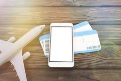 Uno smartphone con uno schermo bianco, due biglietti aerei, un aeroplano fotografie stock libere da diritti