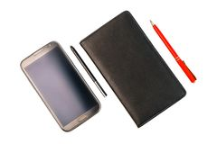 Uno smartphone con una penna dello stilo e un taccuino nero con la penna rossa fotografie stock libere da diritti