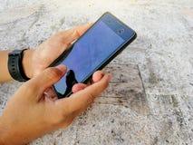 Uno smartphone della tenuta dell'uomo prende una foto immagini stock