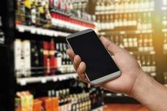 Uno smartphone della tenuta della mano sul deposito del supermercato del vino Fotografia Stock
