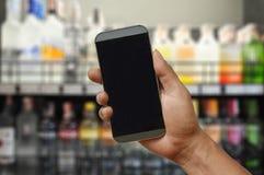 Uno smartphone della tenuta della mano sul deposito del supermercato del vino Immagini Stock